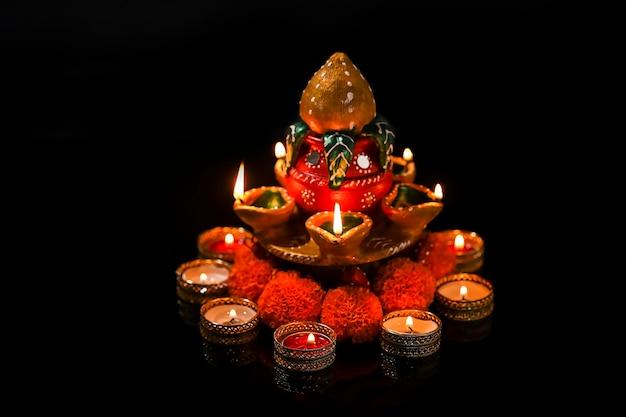 Indisches festival diwali, öllampe und blumenmuster auf dunklem hintergrund