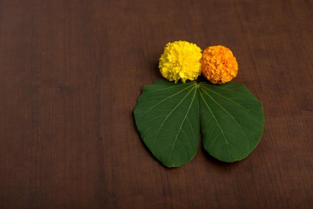 Indisches festival dussehra, das goldenes blatt (bauhinia racemosa) und ringelblumenblumen auf einem braunen hintergrund zeigt.