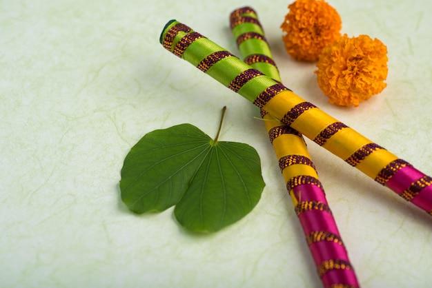 Indisches festival dussehra mit goldenen blättern (bauhinia racemosa) und ringelblumenblüten mit dandiya-stöcken.
