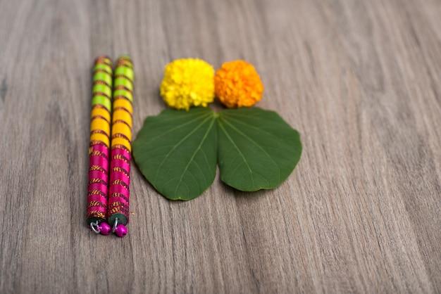 Indisches festival dussehra und navratri, das goldenes blatt (bauhinia racemosa) und ringelblumenblumen mit dandiya-stöcken auf einem hölzernen hintergrund zeigt