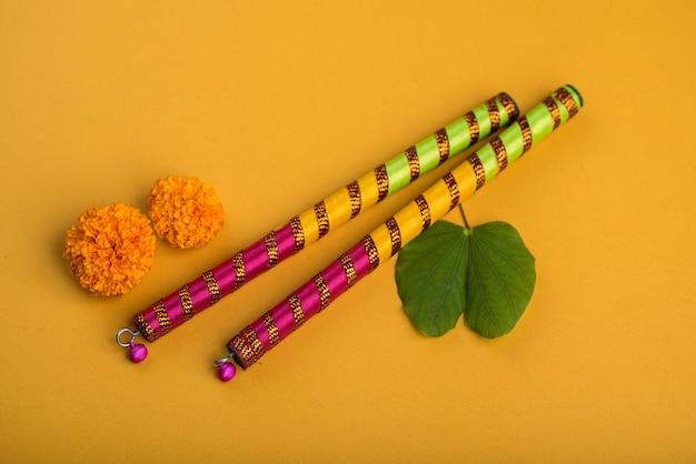 Indisches festival dussehra und navratri mit goldenen blättern (bauhinia racemosa) und ringelblumenblüten mit dandiya-stöcken.