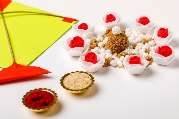 Indisches festival makar sankrant konzept, bunte drachen, schnur und süße sesamkugel.