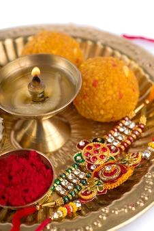 Indisches festival: rakhi mit reiskörnern, kumkum, süßigkeiten und diya auf teller mit einem eleganten rakhi. ein traditionelles indisches armband, das ein symbol der liebe zwischen brüdern und schwestern ist