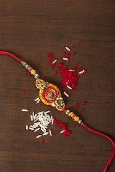 Indisches festival: raksha bandhan feier mit einem eleganten rakhi, reiskörnern und kumkum. ein traditionelles indisches armband, das ein symbol der liebe zwischen brüdern und schwestern ist.