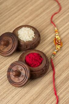 Indisches festival: raksha bandhan mit einem eleganten rakhi, reiskörnern und kumkum. ein traditionelles indisches armband, das ein symbol der liebe zwischen brüdern und schwestern ist.