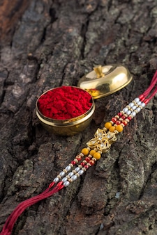 Indisches festival: raksha bandhan mit elegantem rakhi, reiskörnern und kumkum. ein traditionelles indisches armband, das ein symbol der liebe zwischen brüdern und schwestern ist.