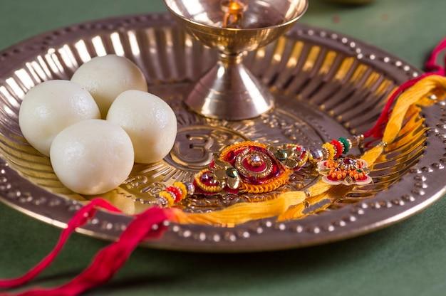 Indisches festival: raksha bandhan oder rakhi hintergrund mit einem eleganten rakhi und diya