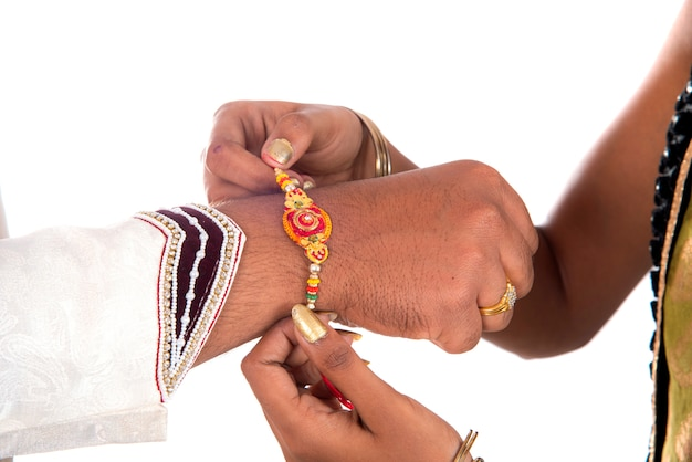 Indisches festival raksha bandhan, raakhi zur hand, schwester binden rakhi als symbol intensiver liebe zu ihrem bruder. Premium Fotos