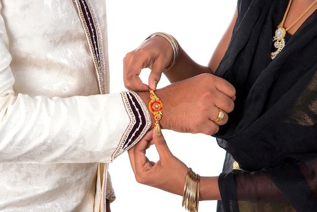 Indisches festival raksha bandhan, raakhi zur hand, schwester binden rakhi als symbol intensiver liebe zu ihrem bruder.