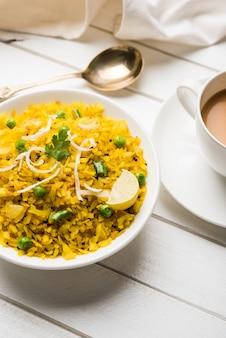 Indisches frühstücksgericht poha auch bekannt als pohe oder aalu poha, bestehend aus geschlagenem reis oder abgeflachtem reis. die reisflocken werden in öl mit gewürzen leicht angebraten und mit heißem tee serviert