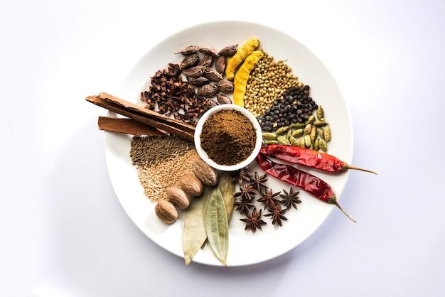 Indisches garam-masala-pulver in schüssel und seine zutaten bunte gewürze. serviert über stimmungsvollem hintergrund. selektiver fokus