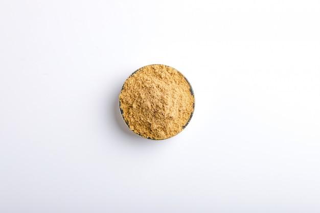 Indisches gewürzkorianderpulver in der schüssel auf weißem hintergrund