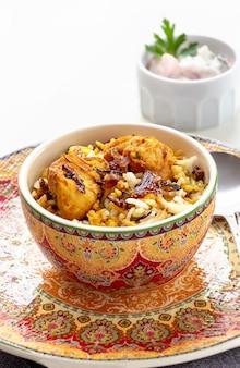 Indisches huhn biryani diente mit jogurttomate raita weißhintergrund. tiefenschärfe.