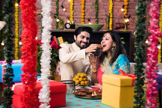 Indisches intelligentes paar, das süßen laddu auf diwali oder jubiläum isst, selektiver fokus