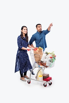 Indisches junges paar mit einkaufswagen oder trolley voller lebensmittel, gemüse und obst. isoliertes foto in voller länge über weißer wand
