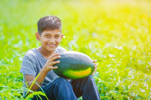 Indisches kind am wassermelonenfeld