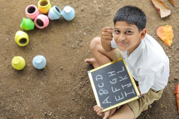 Indisches kind, das abcd-alphabet auf tafel schreibt