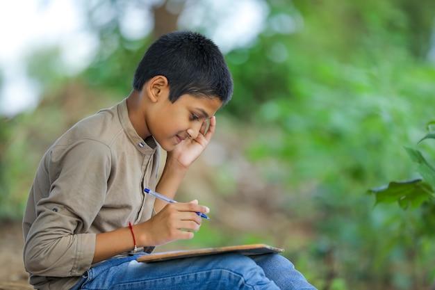 Indisches kind, das auf notizbuch schreibt