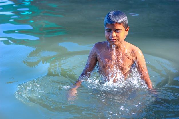 Indisches kind, das im wasser spielt