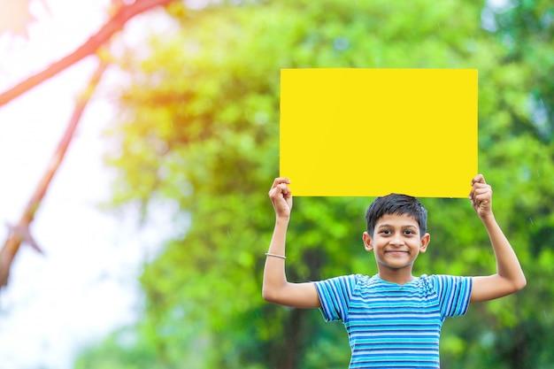 Indisches kind, das leeres plakat hält