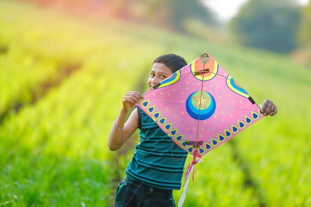 Indisches kind, das mit drachen spielt