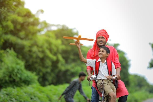 Indisches kind, das mit spielzeugflugzeug mit seinem vater auf fahrrad spielt