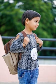 Indisches kind, das schultasche hält