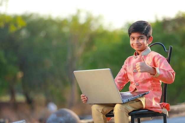 Indisches kind, das traditionelles tuch trägt und laptop verwendet