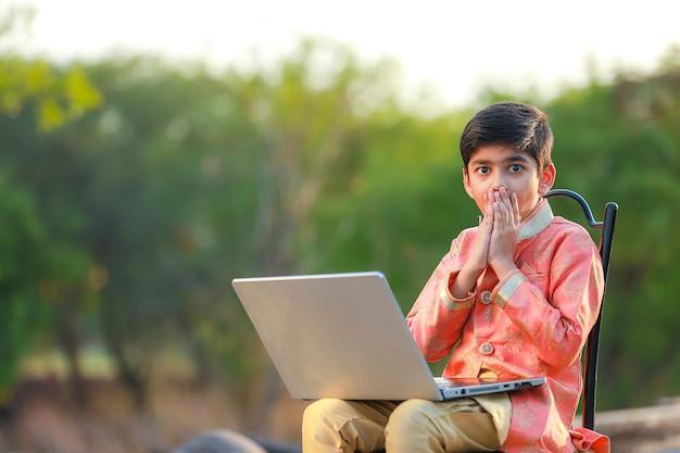 Indisches kind überrascht über einige gute nachrichten im laptop