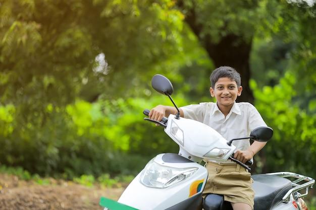 Indisches kleines kind, das motorrad reitet