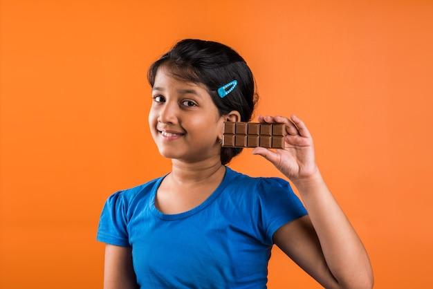 Indisches kleines mädchen, das schokoladentafel isst, lokalisiert über orange hintergrund