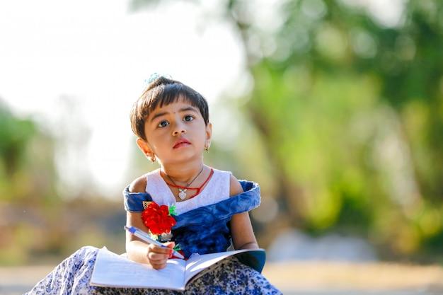 Indisches kleines mädchenkind, das auf notizbuch schreibt, studiert