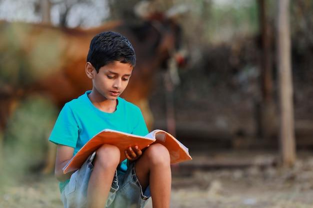 Indisches ländliches kind, das ein buch liest