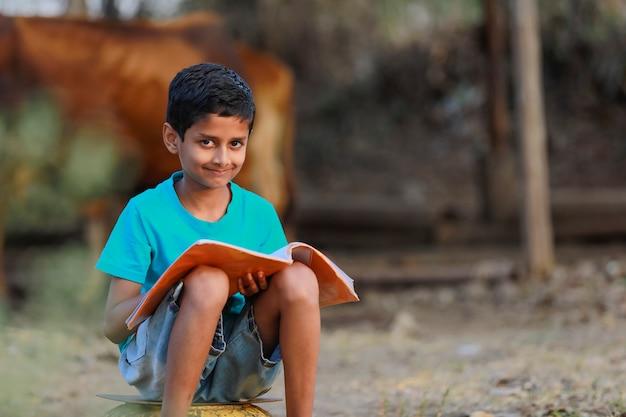Indisches ländliches kind mit einem buch