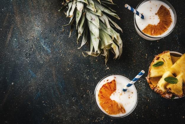 Indisches lebensmittel und getränk karamellisierter dunkelblauer hintergrund des ananas lassi-cocktails