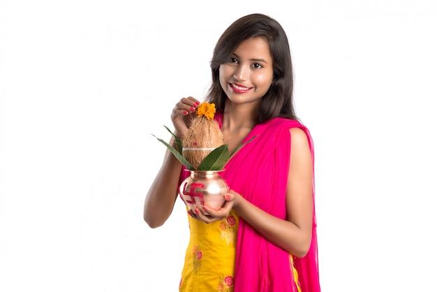 Indisches mädchen, das ein traditionelles kupfernes kalash, ein indisches festival, ein kupfernes kalash mit kokosnuss und ein mangoblatt mit der blumendekoration, wesentlich in hinduistischem pooja hält.