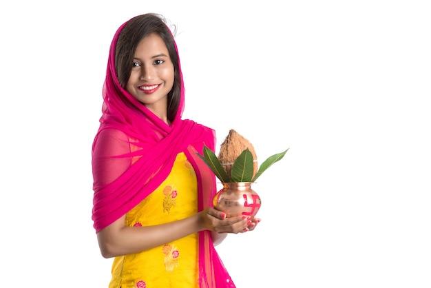 Indisches mädchen, das eine traditionelle kupfer-kalash, indisches festival, kupfer-kalash mit kokosnuss- und mangoblatt mit blumendekor hält, essentiell in hindu pooja.