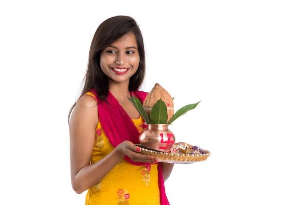 Indisches mädchen, das eine traditionelle kupferne kalash mit pooja thali hält