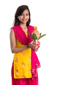 Indisches mädchen, das einen traditionellen kupfer-kalash, indisches festival, kupfer-kalash mit kokosnuss- und mangoblatt mit blumendekor hält, essentiell in hindu pooja.