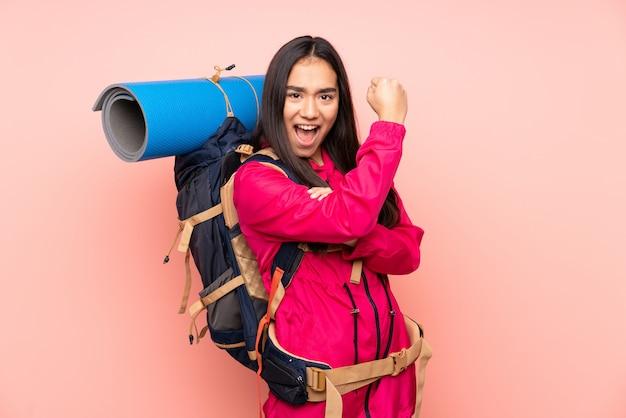 Indisches mädchen des jungen bergsteigers mit einem großen rucksack lokalisiert auf rosa wand, die starke geste macht