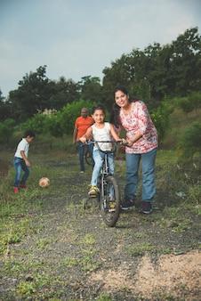 Indisches mädchen lernt fahrrad fahren, balancieren