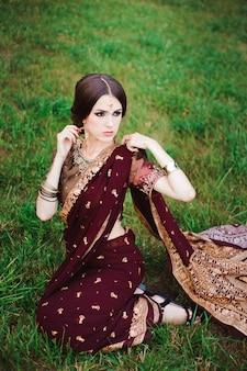 Indisches mädchen mit orientalischem schmuck und make-up-henna auf die hand aufgetragen. brunette hindu model girl mit indischen juwelen