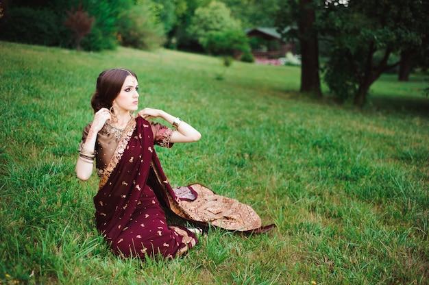 Indisches mädchen mit orientalischem schmuck und make-up-henna auf die hand aufgetragen. brunette hindu model girl mit indischen juwelen.