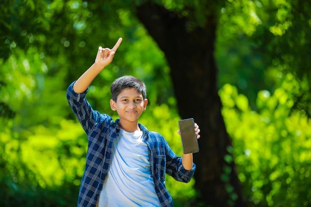 Indisches niedliches kind, das smartphone zeigt