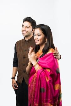 Indisches paar begrüßt mit namaskara-pose oder beiden händen gefaltet, während es traditionelle festkleidung trägt, isoliert auf weißem hintergrund