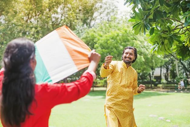 Indisches paar, das am tag der republik indien einen dreifarbigen drachen der indischen flagge fliegt
