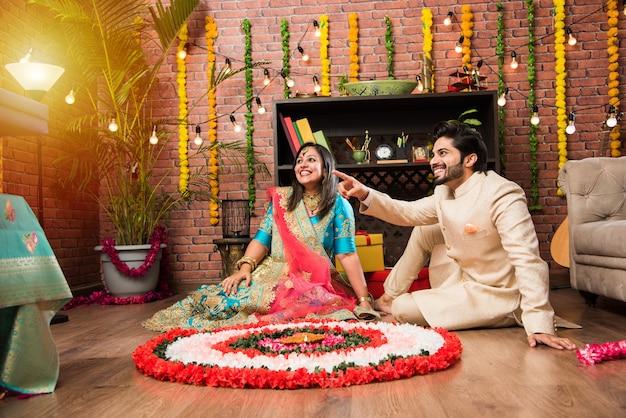 Indisches paar macht rangoli auf diwali oder onam festival, macht selfie oder hält süßigkeiten?