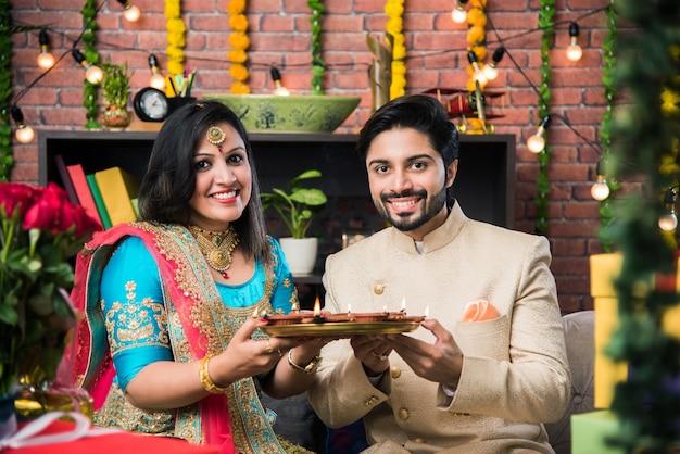 Indisches paar mit diya, süßigkeiten und geschenken beim feiern des diwali-, deepavali- oder dipavali-festivals