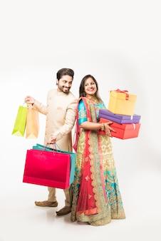 Indisches paar mit einkaufstüten und geschenkboxen, isoliert auf weißem hintergrund