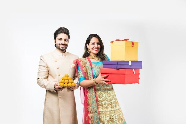 Indisches paar mit laddu und geschenkboxen auf diwali oder festival, isoliert über weißem hintergrund. traditionelle kleidung tragen
